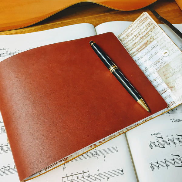 brown leather stave notation book with sheet music lining and mont blanc pen