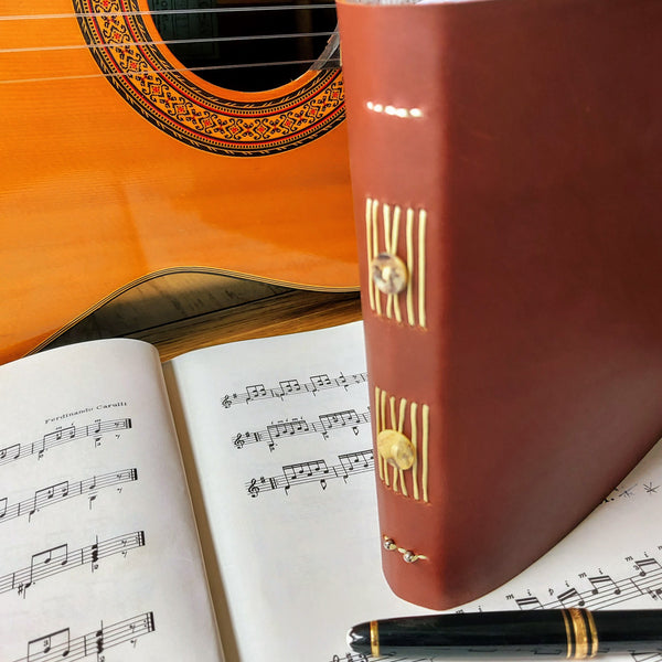 Bespoke Bindery leather music journal with button trim on spine by guitar and pen