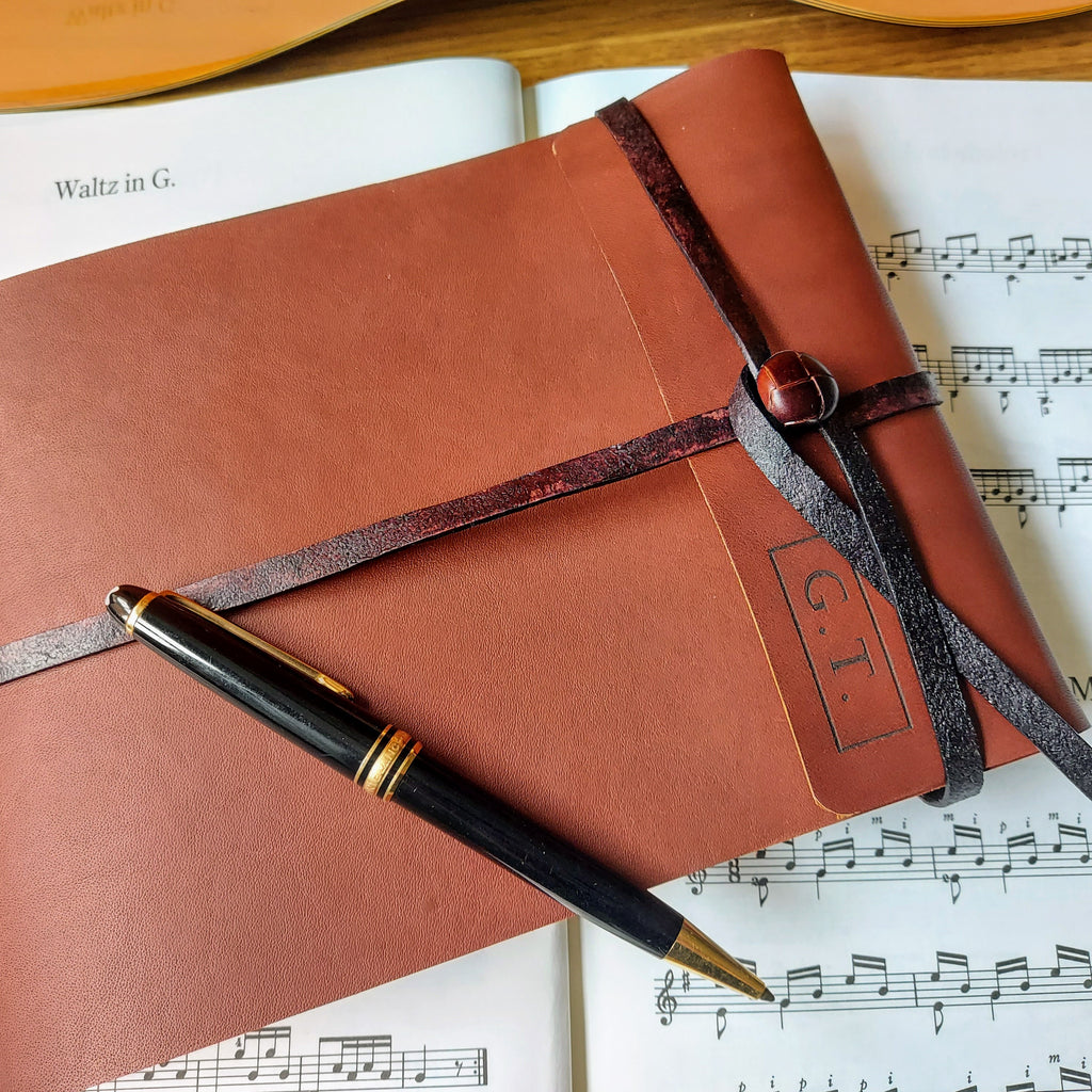 leather trifold music stave journal with leather strap and button fastening, mont blanc pen and sheet music