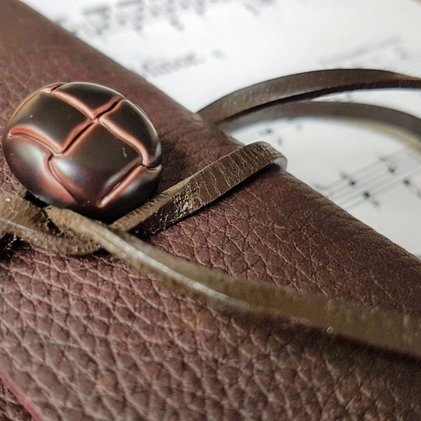 close up of leather button and strap used to fasten leather music composition journal