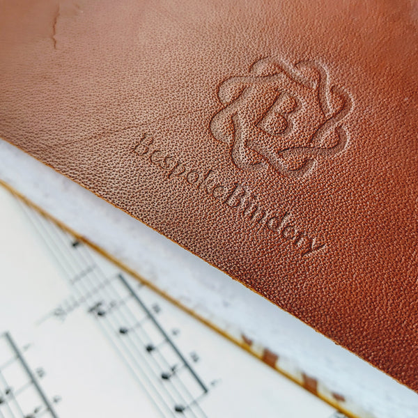 Bespoke Bindery logo branded into the leather on reverse of music journal