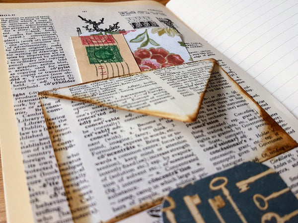 Handmade Junk Journal page with vintage dictionary envelope pocket and tags