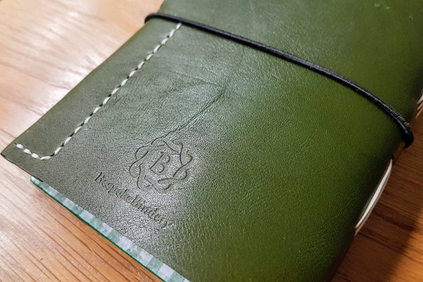 Hunting Shooting journal in glossy green spanish leather showing rear cover leather pencil pocket and bespoke bindery logo