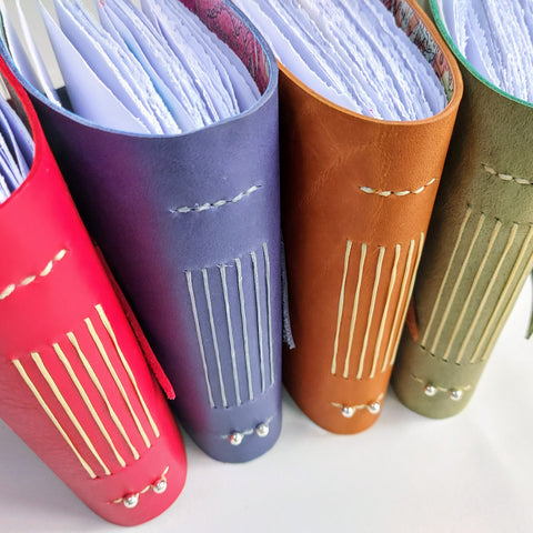 4 brightly coloured leather travel journals, red leather, purple leather, brown leather, green leather
