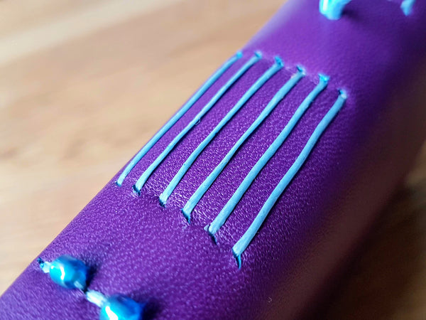 Purple leather travel journal with pale blue hand stitched spine with glass beads