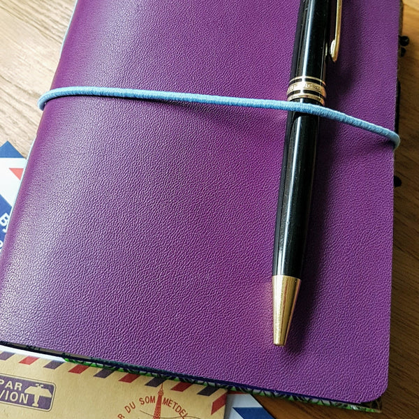 Purple leather travel journal with pale blue elastic loop closure