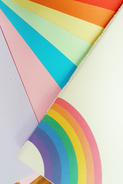 Ivory hand stitched card cover with rainbow logo and rainbow variety coloured pages by BespokeBindery