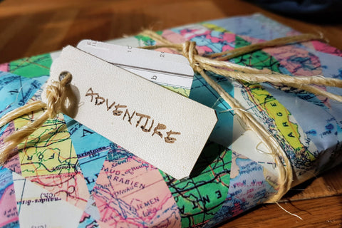 Add gift wrap with map themed wrapping paper, tied with twine and trimmed with leather tag saying Adventure