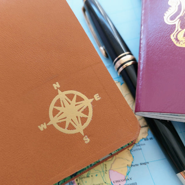 Gold foil compass showing 4 major cardinal compass points on golden brown leather travel journal by Bespoke Bindery
