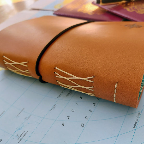 BespokeBindery hand stitched spine on leather bucket list travel journal.  Elastic loop fastener