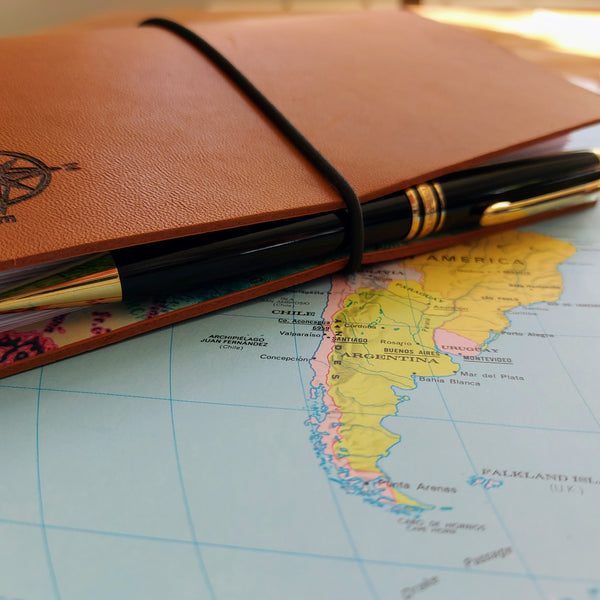 leather travel journal fastens with elastic loop which serves as a pen holder
