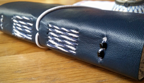 Blue and White stitching and small black beads on the spine of Navy Leather Journal