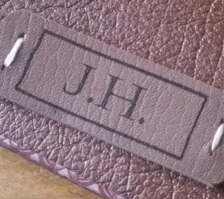 laser etched monogram stitched and glued into place