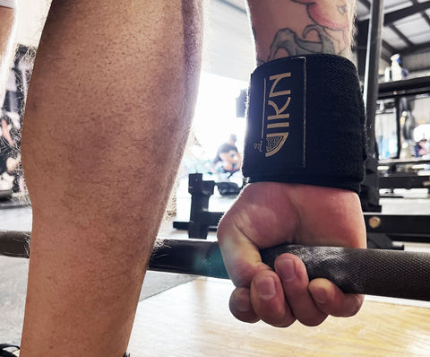 Man using hookgrip to deadlift at a powerlifting gym wearing VIKN wrist wraps.