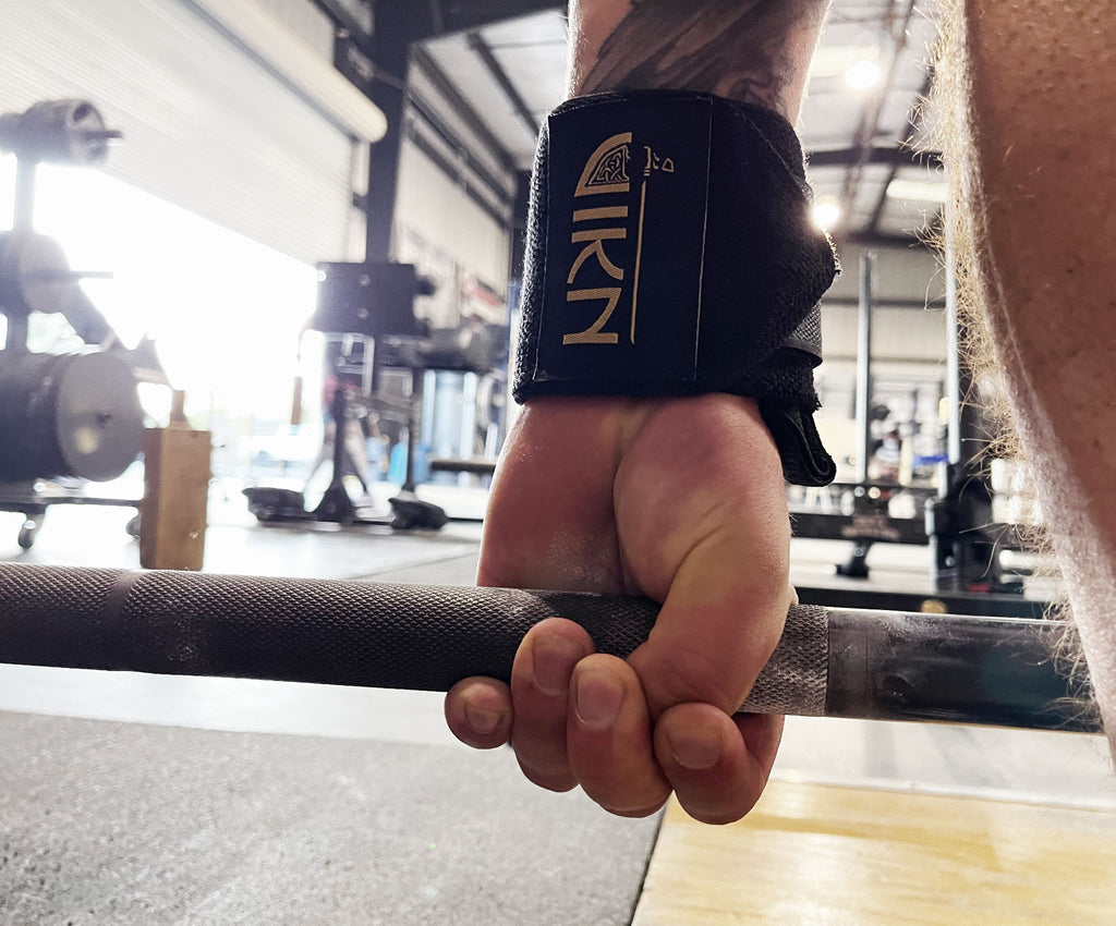 Man in powerlifting gym using hookgrip for deadlifts wearing VIKN wrist wraps.