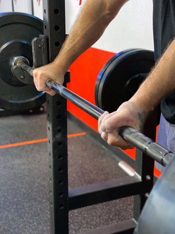 man alternate gripping barbell