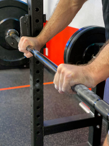 man doing a double overhand pronated grip on barbell