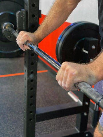 man using a hook grip on a barbell