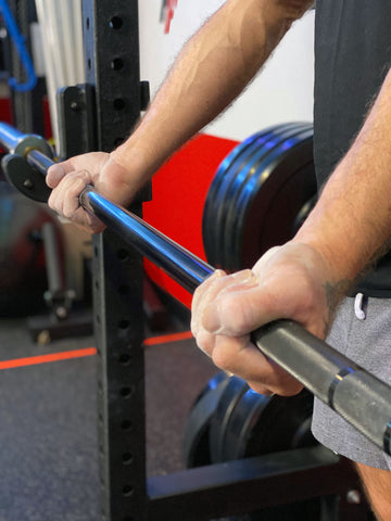 man performing an underhand supinated barbell grip