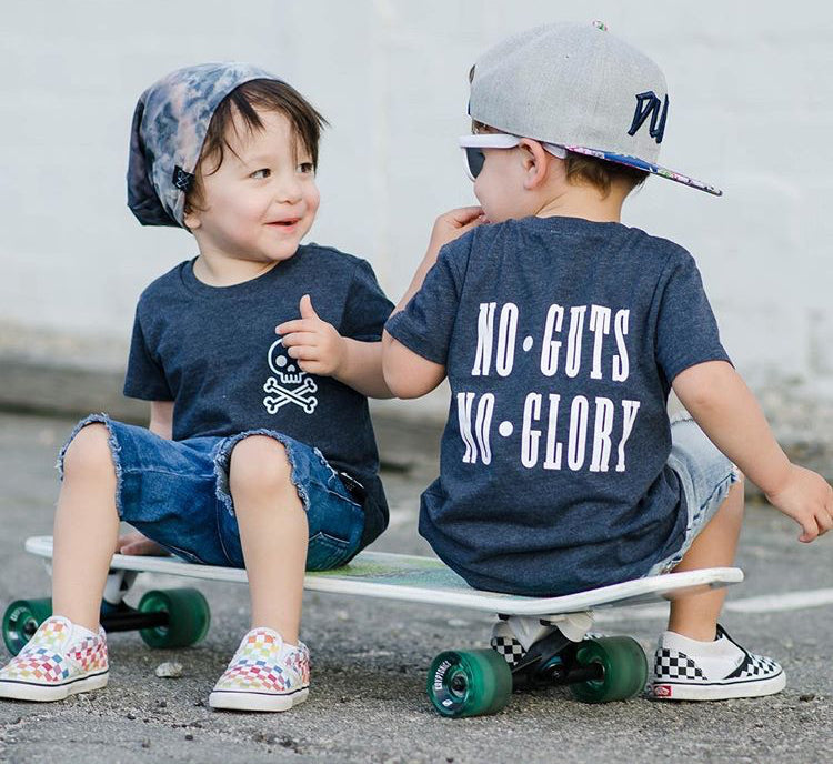 two kids wearing TRILOGY DESIGN No Guts No Glory T-shirt sitting on skateboard