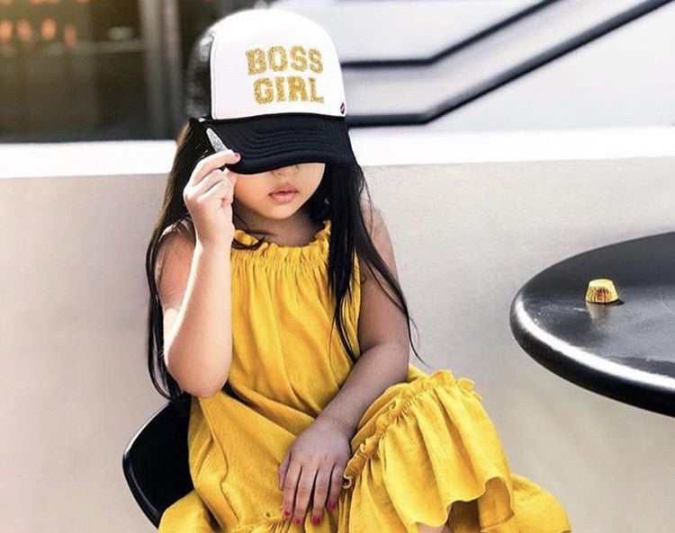 Girl in yellow dress and trucker hat. Kids Accessories.