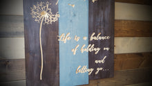"Load image into Gallery viewer, Carved Dandelion Sign ""Life is a balance of holding on and letting go"