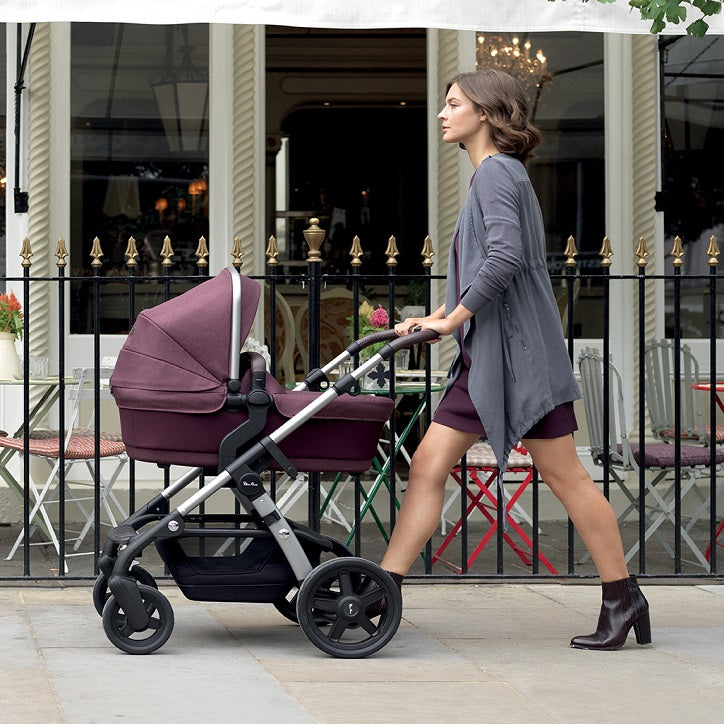 Woman Pushing the Silver Cross Wave Stroller with Bassinet in Claret