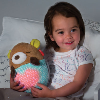 toddler holding the Skip Hop Moonlight & Melodies Hug Me Projection Soother Bear