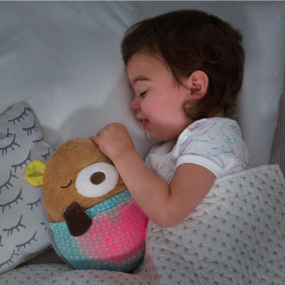 toddler sleeping with the Skip Hop Moonlight & Melodies Hug Me Projection Soother Bear
