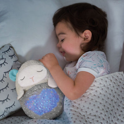 toddler sleeping with the Skip Hop Moonlight & Melodies Hug Me Projection Soother Lamb