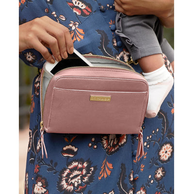 Mom wearing the Skip Hop Greenwich Convertible Hip Pack in Dusty Rose