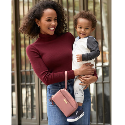 Mom wearing the Skip Hop Greenwich Convertible Hip Pack in Dusty Rose as a wristlet