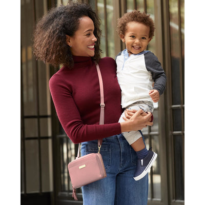 Mom wearing the Skip Hop Greenwich Convertible Hip Pack in Dusty Rose as a crossbody bag