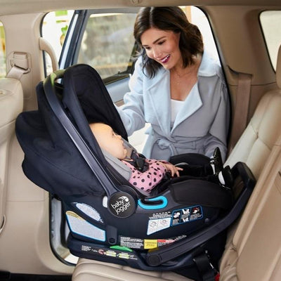 Mom placing Baby Jogger City Go 2 infant car seat in the car