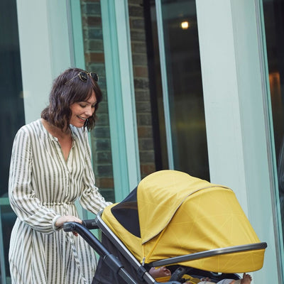 Mom pushing the Diono Quantum² Stroller in Yellow Sulphur