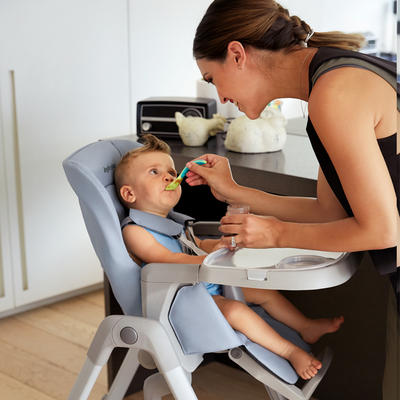 Mom feeding infant in the Inglesina MyTime High Chair in Sugar