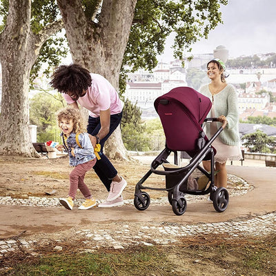 Mom pushing the Maxi-Cosi Tayla Stroller in Essential Red