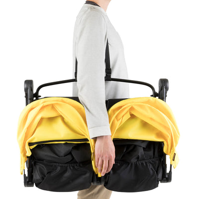 mom carrying Mountain Buggy Nano Duo Stroller in Cyber folded