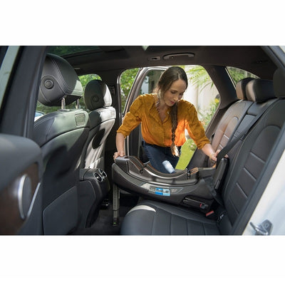 Mom positioning the Nuna PIPA RELX Infant Car Seat Base in the car
