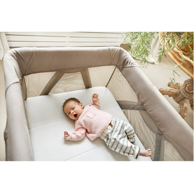 Baby sleeping in the Nuna SENA™ Aire Mini Travel Crib in Champagne