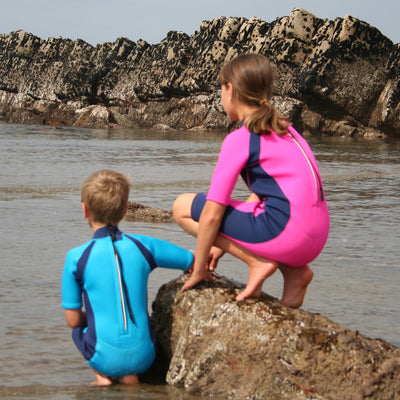 Children at the beach wearing Konfidence Shorty Wetsuits