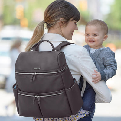 Mom holding baby with the Skip Hop Flatiron Diaper Backpack