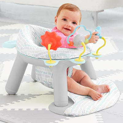 Baby playing in the Skip Hop Silver Lining Cloud 2-In-1 Activity Infant Seat