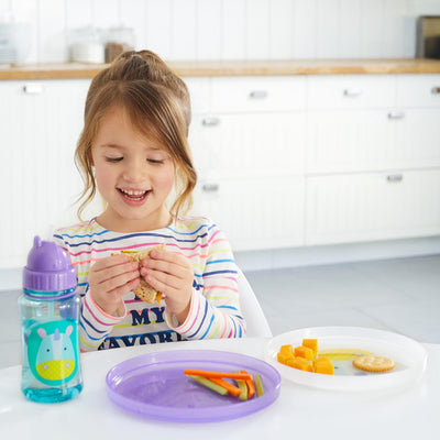 Girl eating from the Skip Hop Zoo Smart Serve Non-Slip Plates in Unicorn