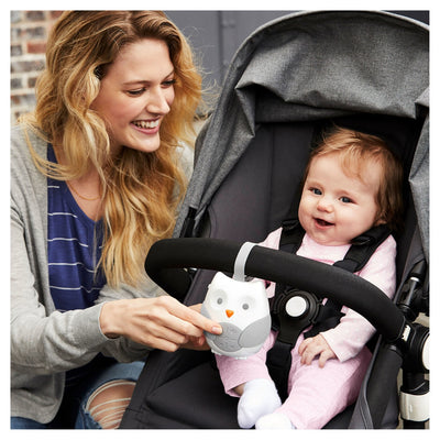 Mom and baby in stroller with Skip Hop Stroll & Go Portable Baby Soother hanging from stroller bar