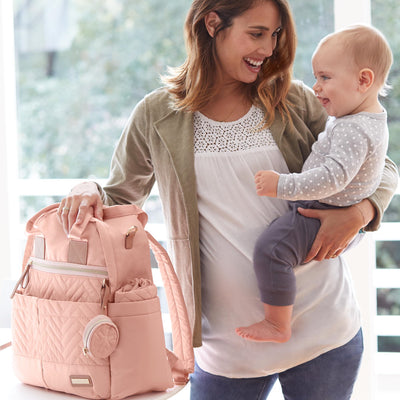 Mom and baby with the Skip Hop Suite 6-In-1 Diaper Backpack Set in Blush