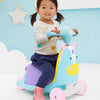 Little girl riding on the Skip Hop Zoo 3-In-1 Ride On Toy in Unicorn