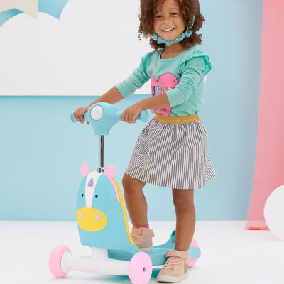 Girl scooting on the Skip Hop Zoo 3-In-1 Ride On Toy in Unicorn