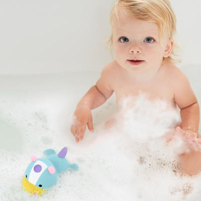 Baby playing with Skip Hop Zoo Light Up Bath Toy in Unicorn