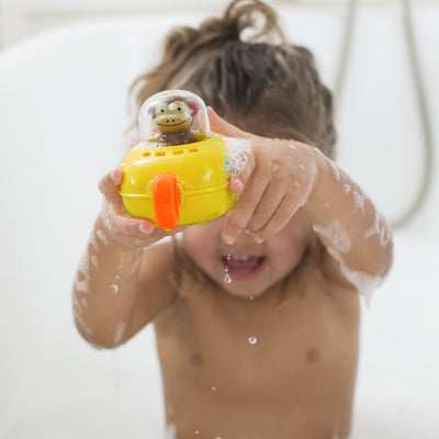 Little girl playing in the bath with Skip Hop Zoo Pull & Go Monkey Submarine